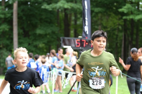 Cole Mullarkey and Angelo Reade, both 9, cross the finish line at their first 4-mile run.